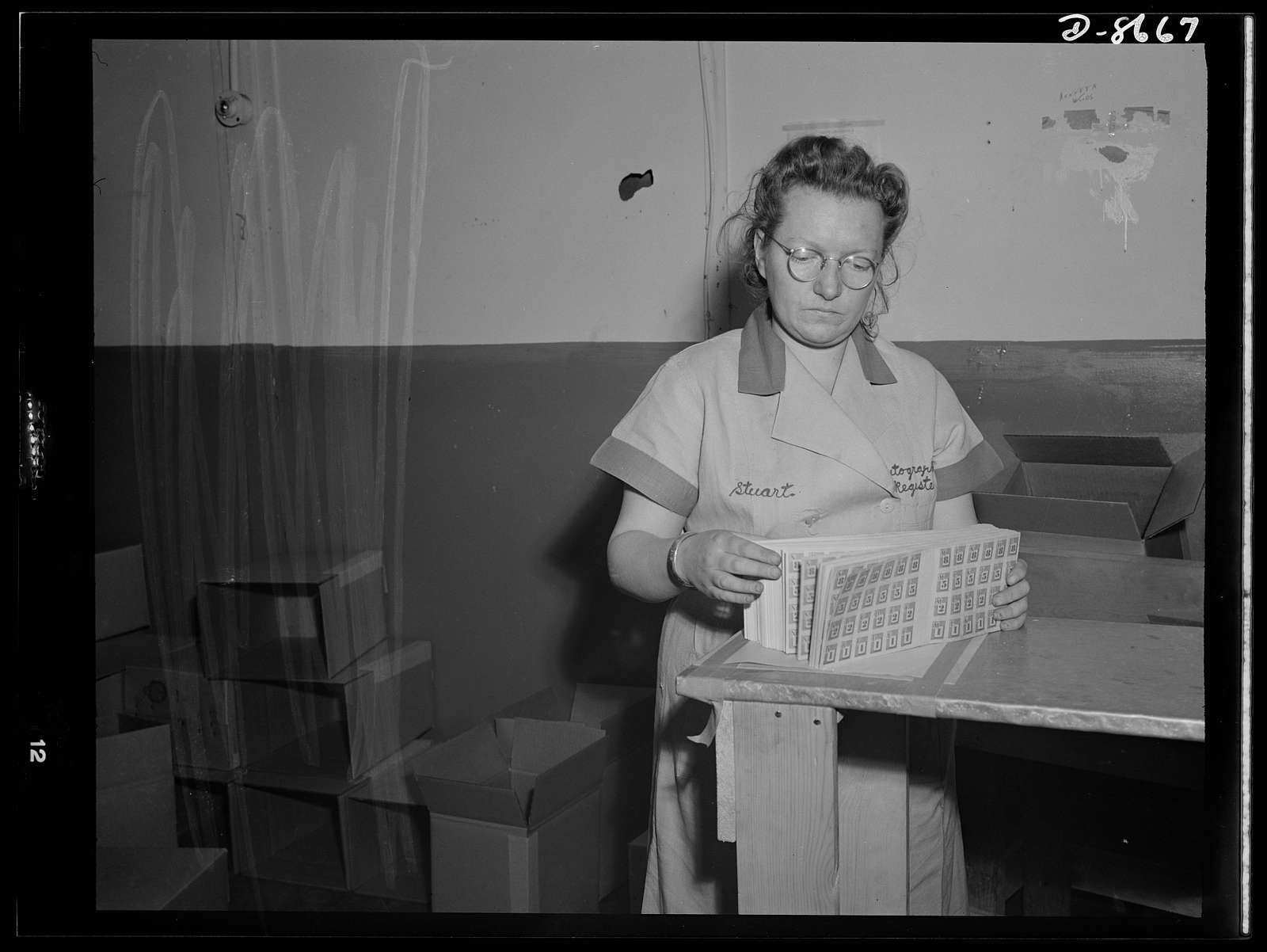 Printing war ration book 2. Ida Stuart quickly checks the assembled pages of ration books as they come from the cutter