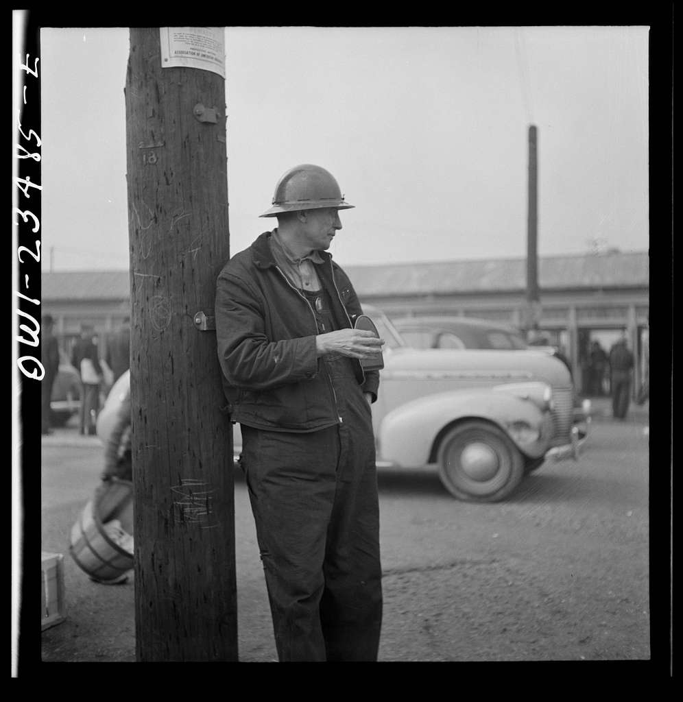 Bethlehem-Fairfield shipyards, Baltimore, Maryland. A shipyard worker looking at a time clock from outside of the yard