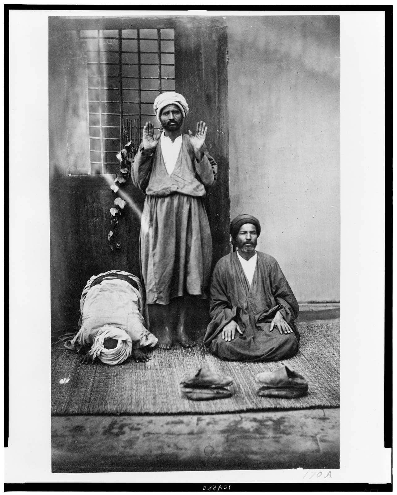 [Cairo(?). Three indigenous people in prayer]