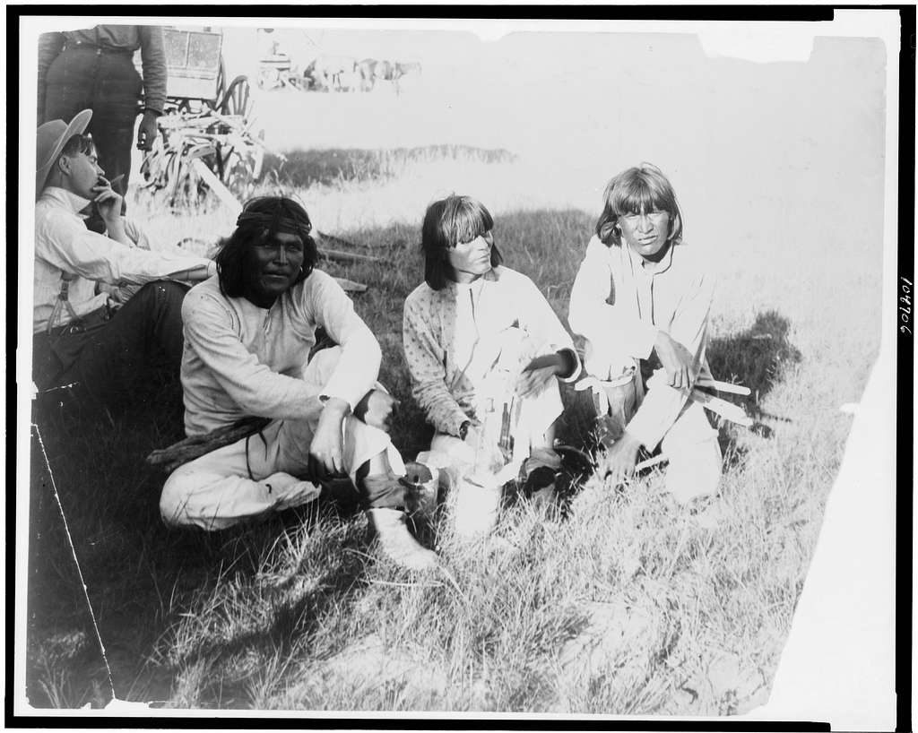 [Thrasher(?) and three Indians sitting outdoors]