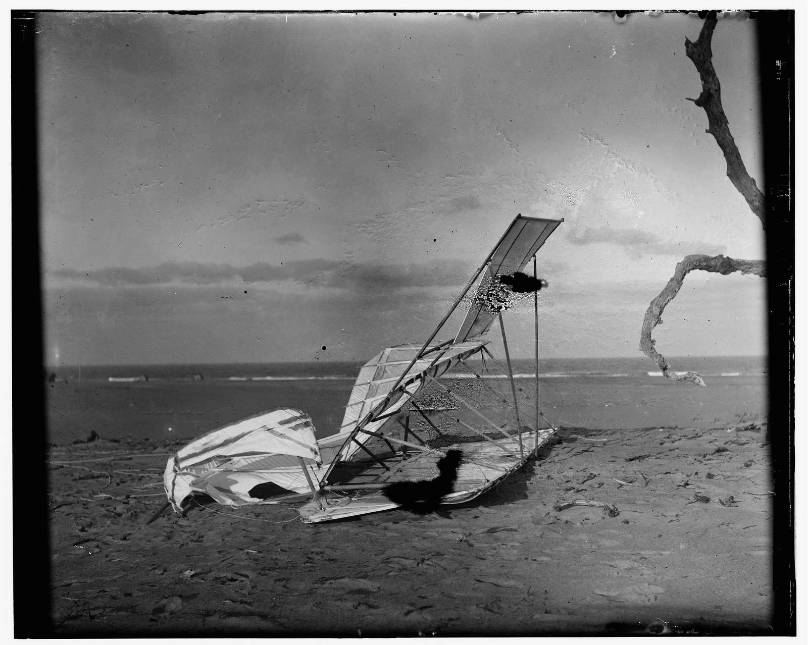 [Crumpled glider wrecked by the wind on Hill of the Wreck (named after a shipwreck)]