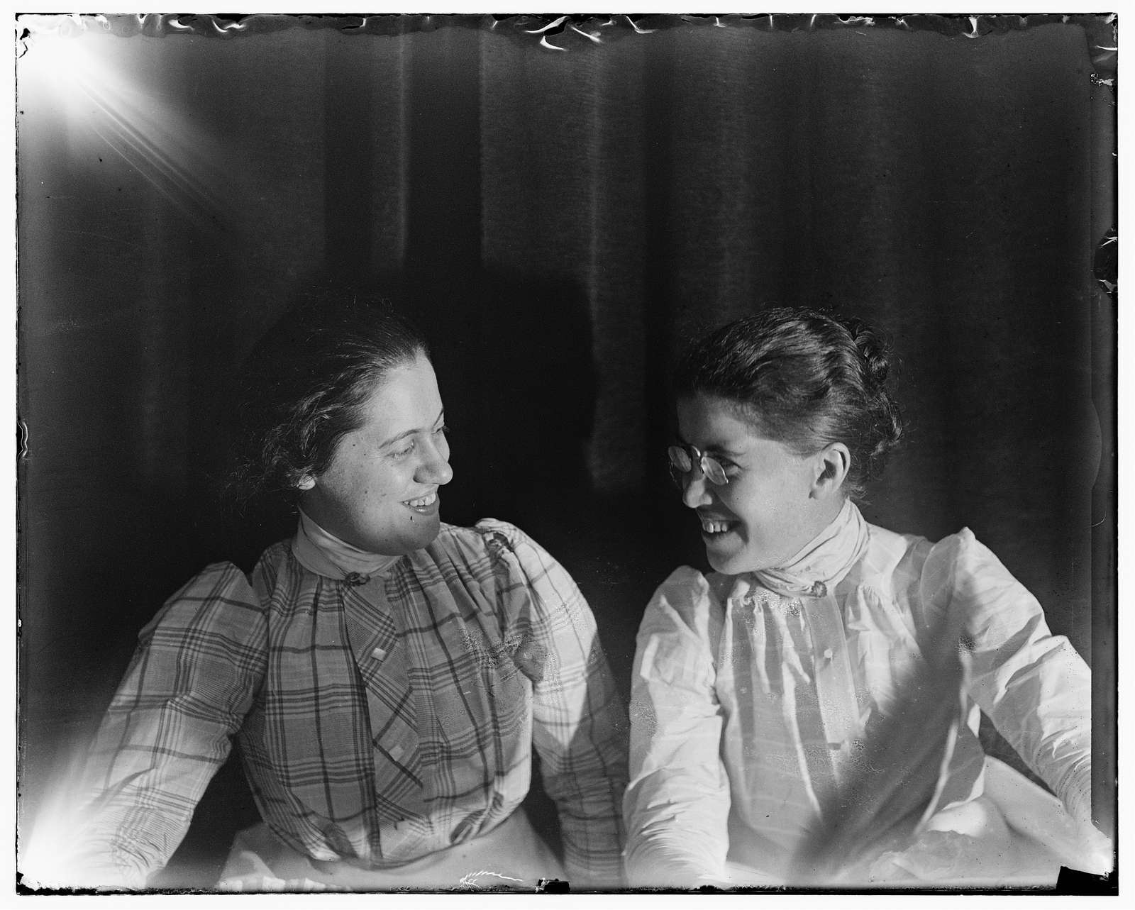 [Katharine Wright and friend Harriet Silliman, half length, smiling and facing each other]